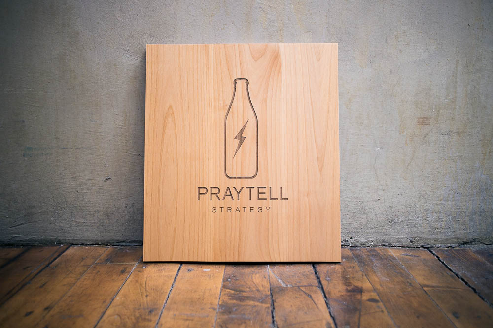 Etched wood sign for Praytell Strategy