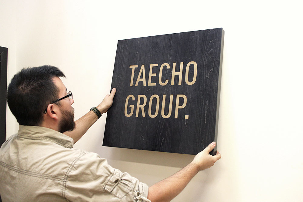 Laser etched black wood sign for Taecho Group