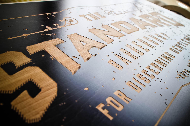 The Standard Barbershop Etched Black Wood Sign