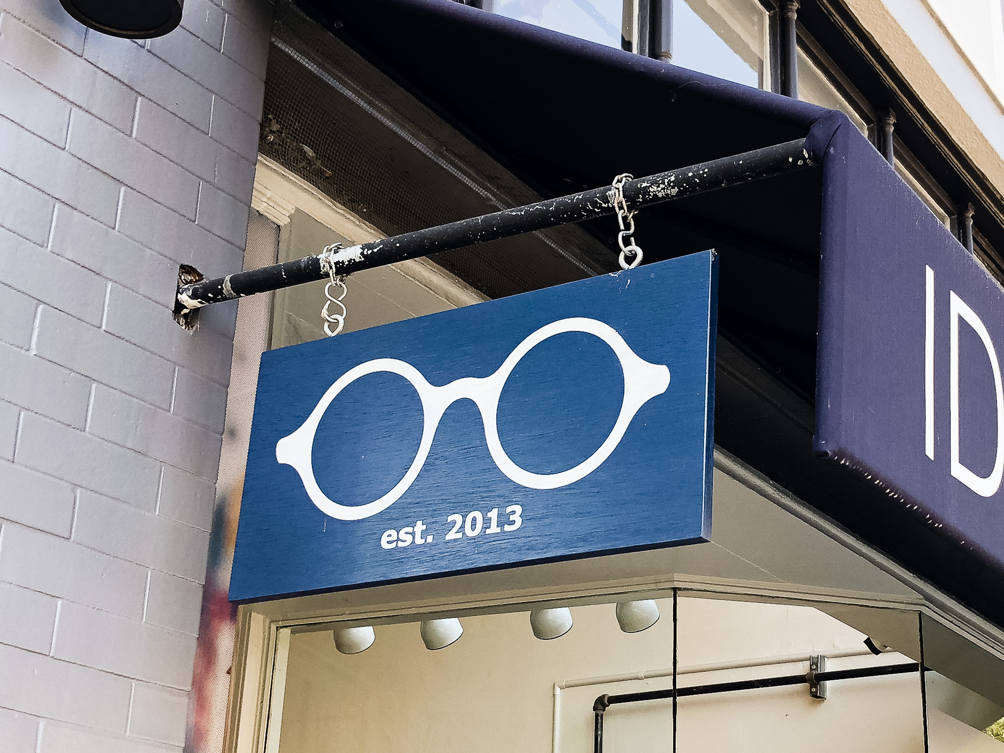 optometry glasses retail store simple modern outdoor hanging sidewalk sign