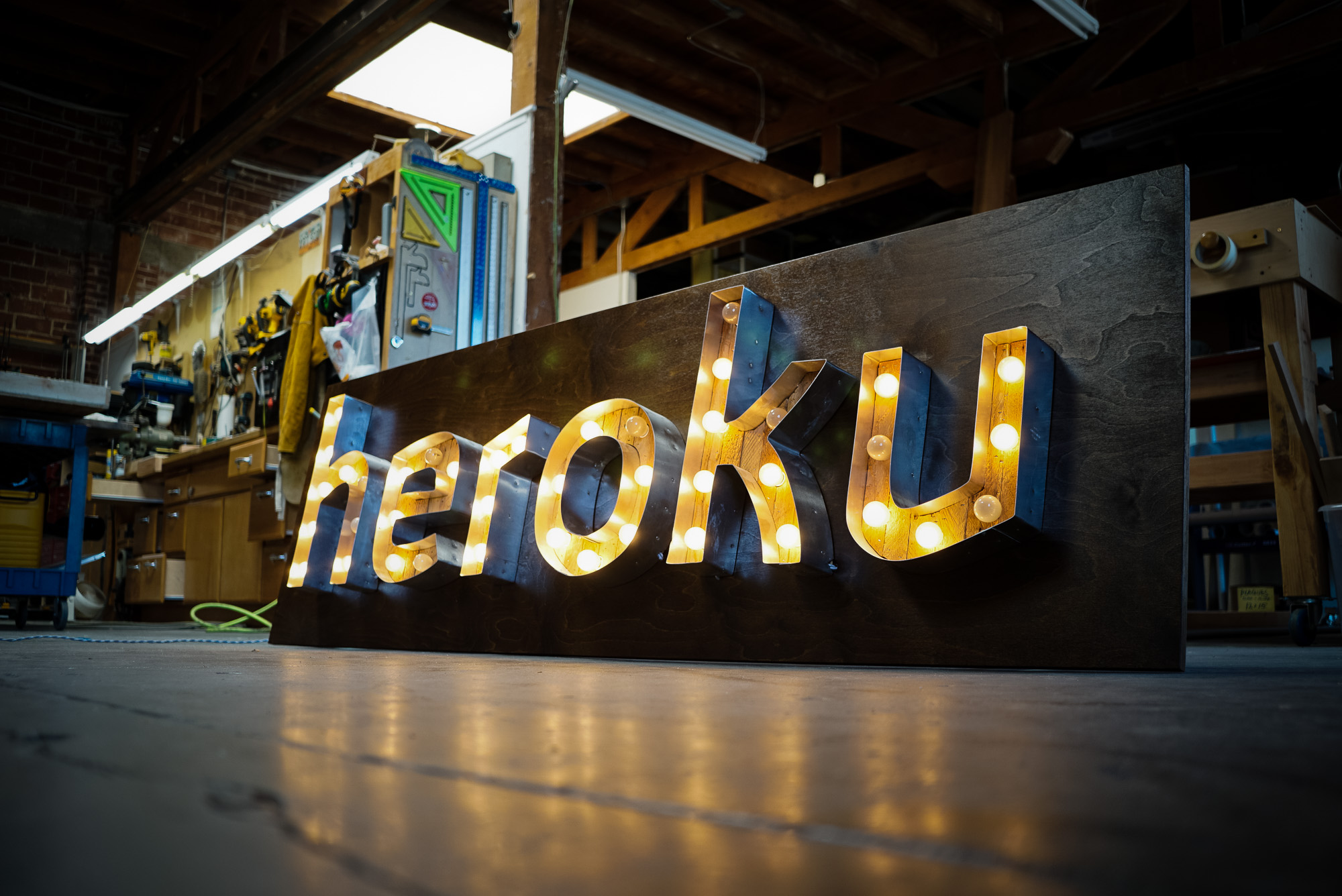 vintage / retro illuminated marquee sign with reclaimed wood and bulbs for tech / startup office, Heroku