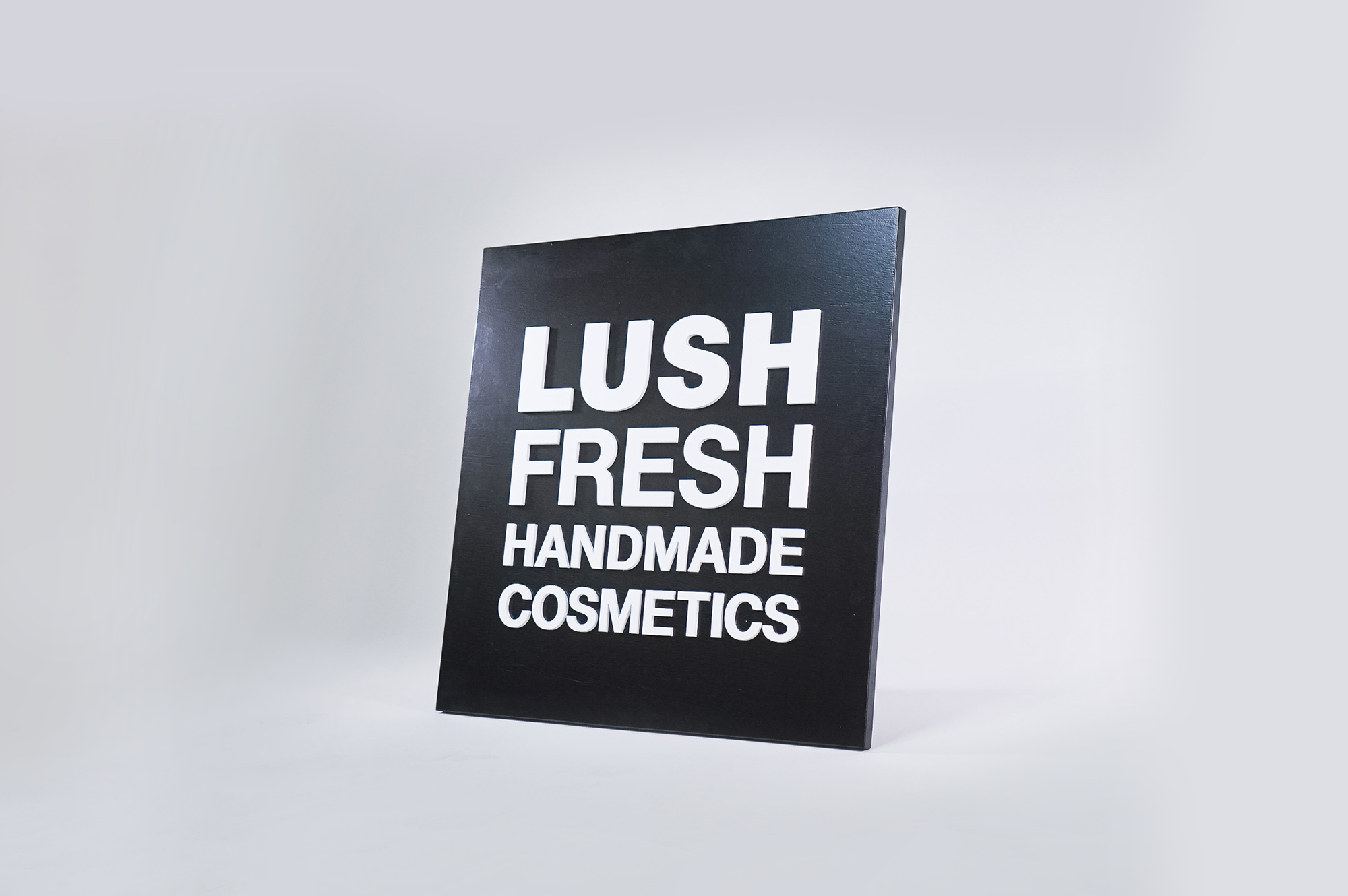 Lush hanging retail blade sign in black stained wood with raised dimensional white letters