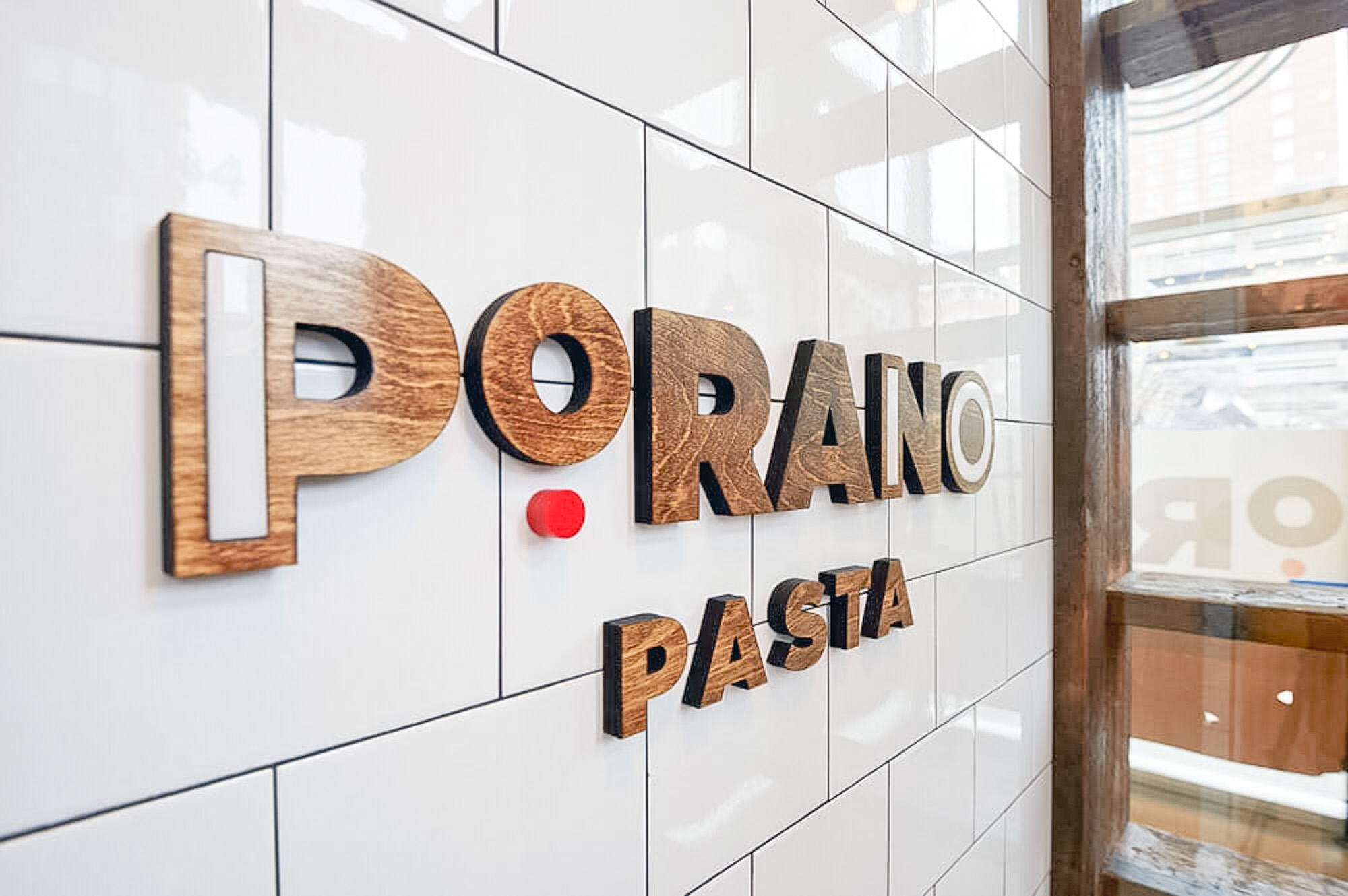 Porano Pasta dark wood and colored wood restaurant wall sign on white tile
