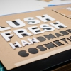 Lush hanging retail blade sign in black stained wood with raised dimensional white letters - process