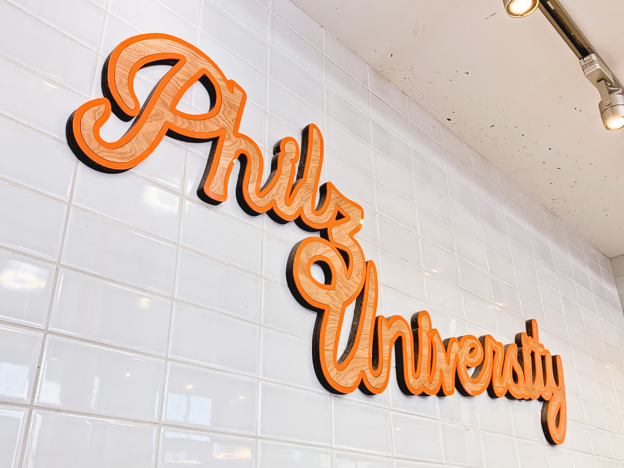 Orange and light wood script sign on white tile wall for Philz University in San Francisco