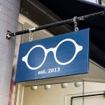 optometry glasses retail store simple modern outdoor hanging sidewalk sign