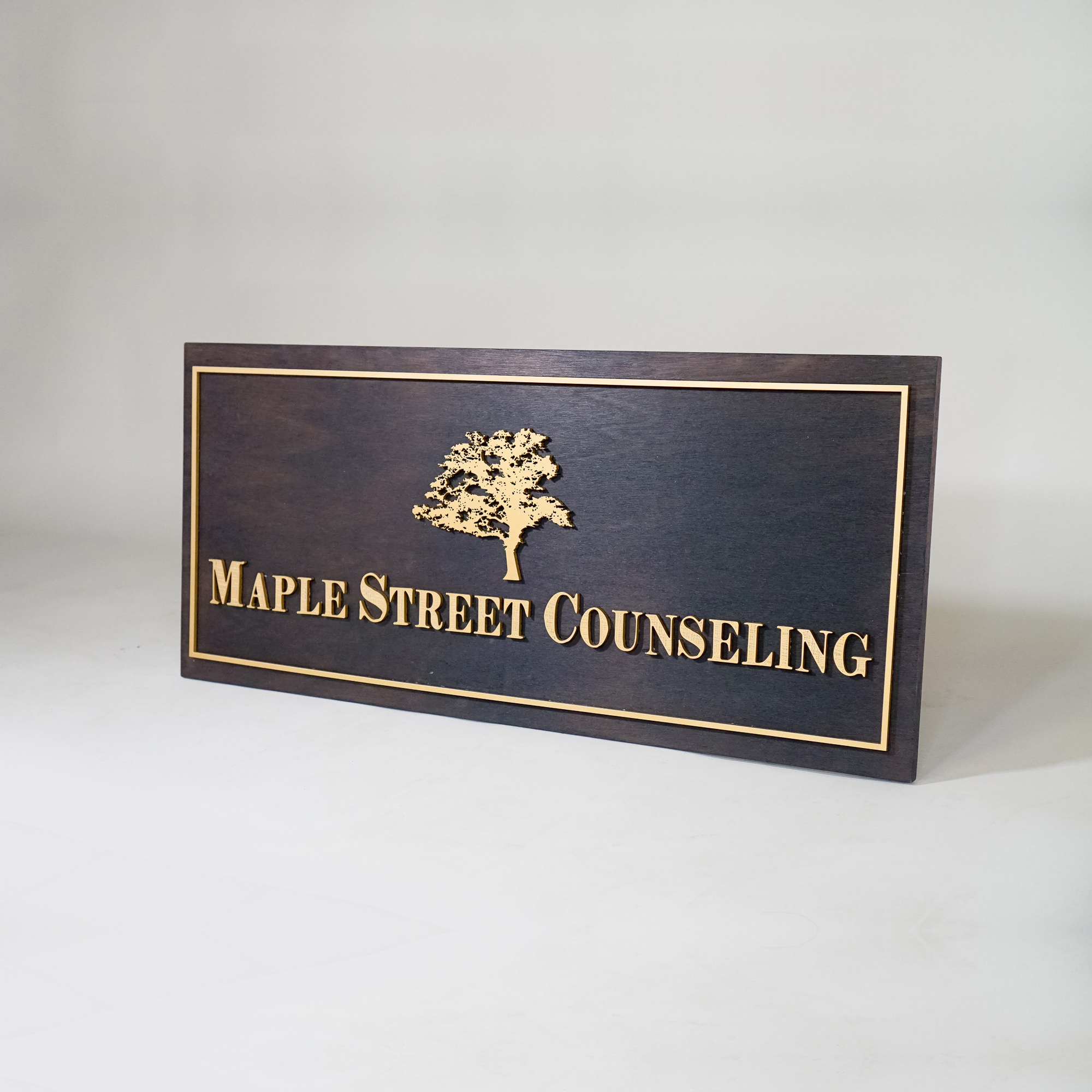 Maple Street Counseling Gold artwork on torched wood