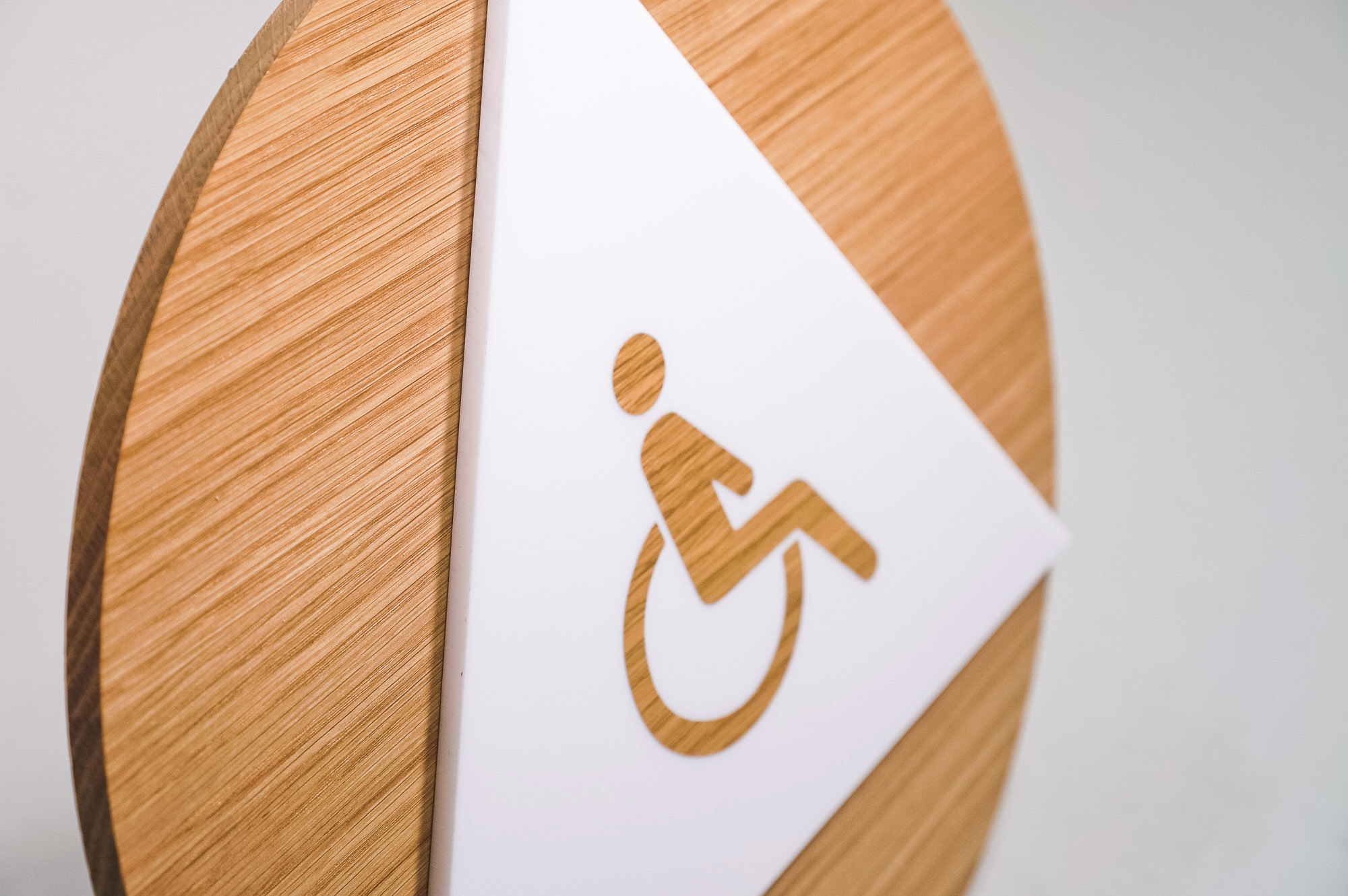Modern light wood and white handicap ADA restroom signs for Slack, a cloud-based set of proprietary team collaboration tools and services.