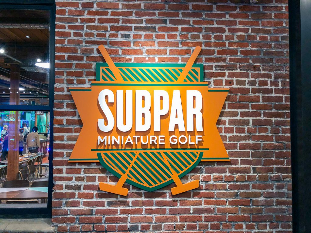 Subpar Mini Golf colorful painted sign on brick wall