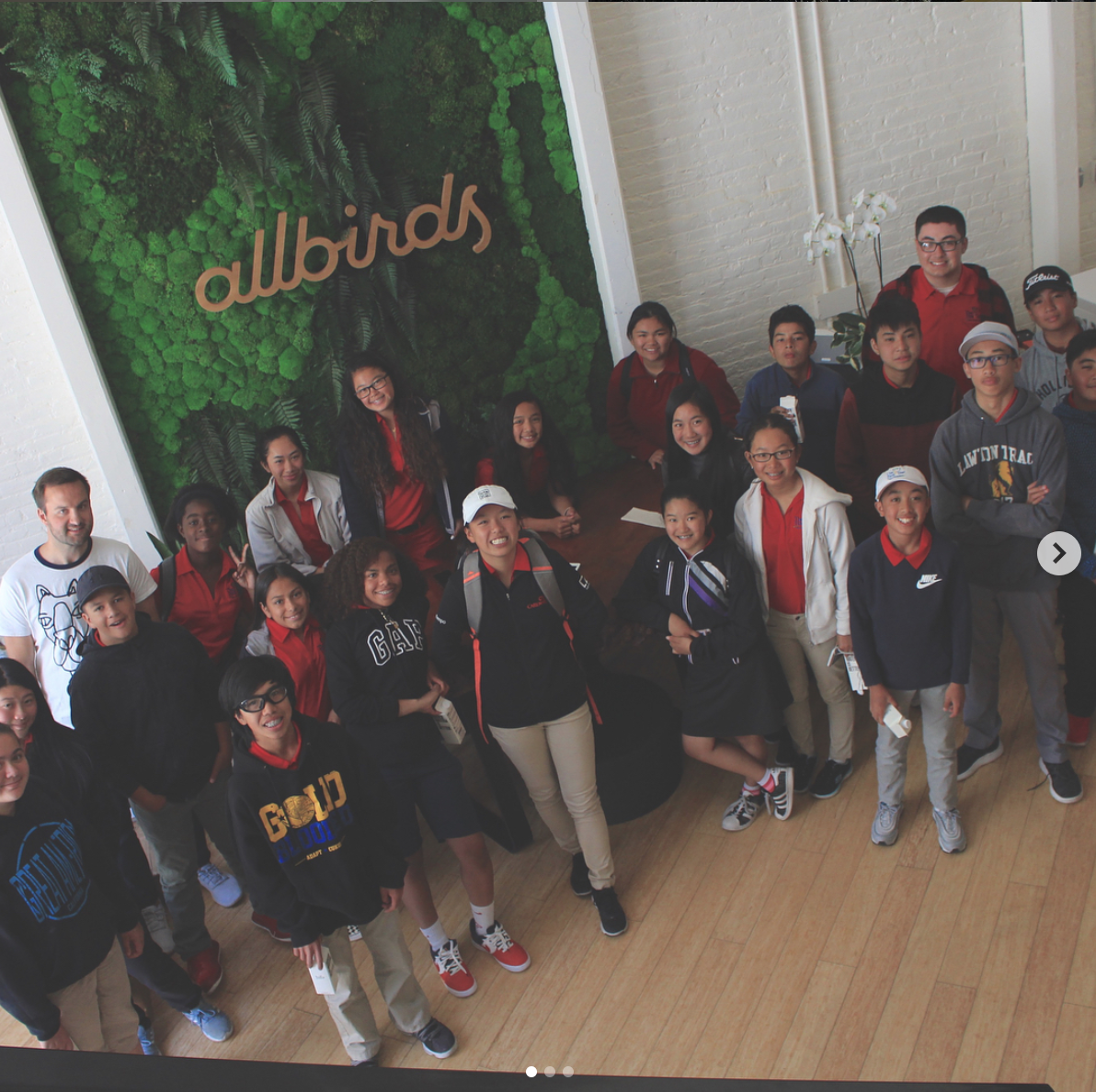 Group posing with light wood script sign on moss wall at Allbirds, a San Francisco-based direct-to-consumer startup aimed at designing environmentally friendly footwear.