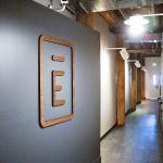 Dark wood company logo on grey wall at Envoy, a San Francisco based tech company that creates visitor management software.