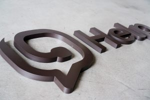 Clean and modern bronze painted lobby sign for Help.com