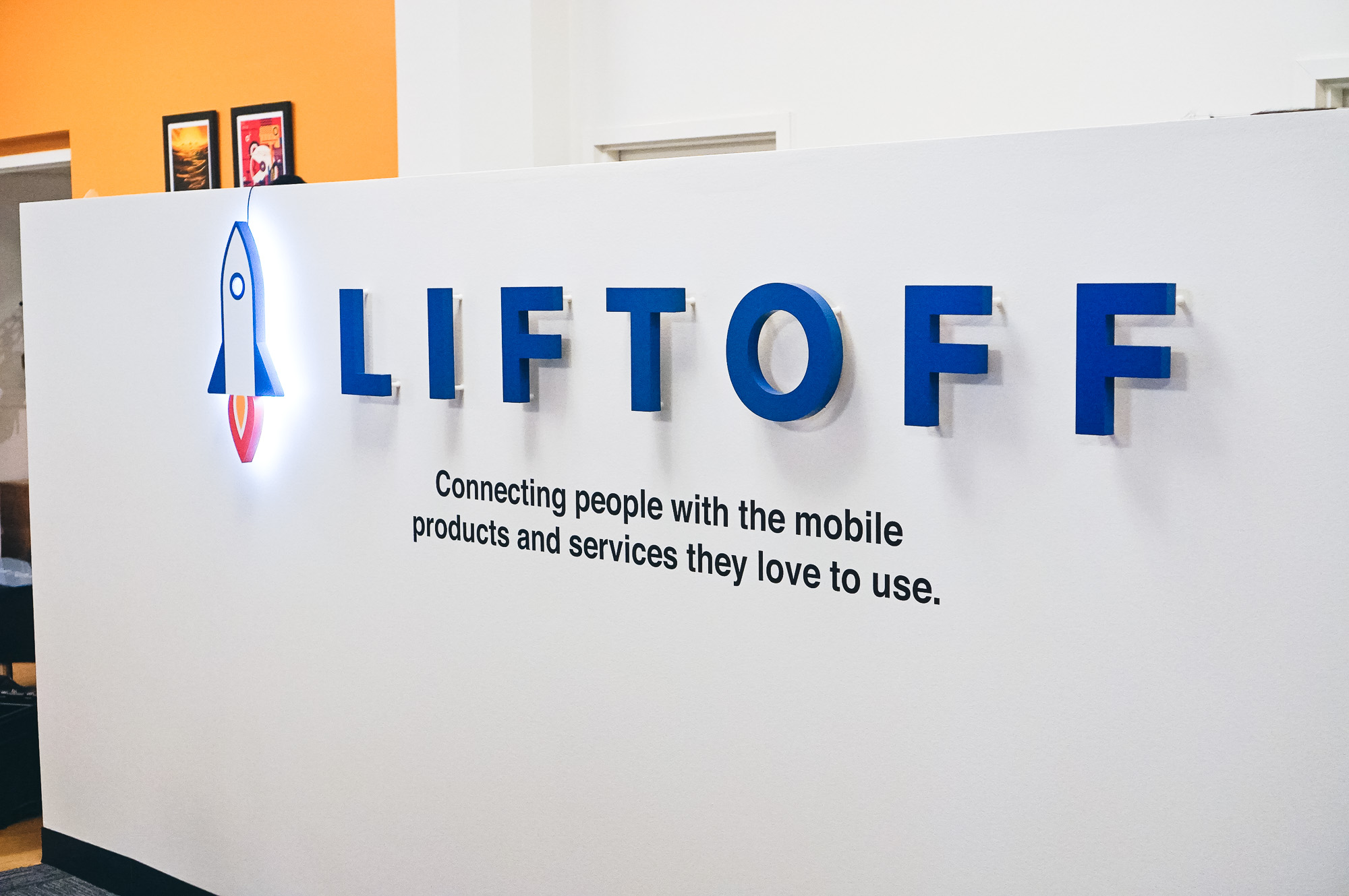 Illuminated rocket logo sign for Liftoff, a company that creates a mobile app optimization marketing platform. Office designed by Knotel, an office space rental agency.