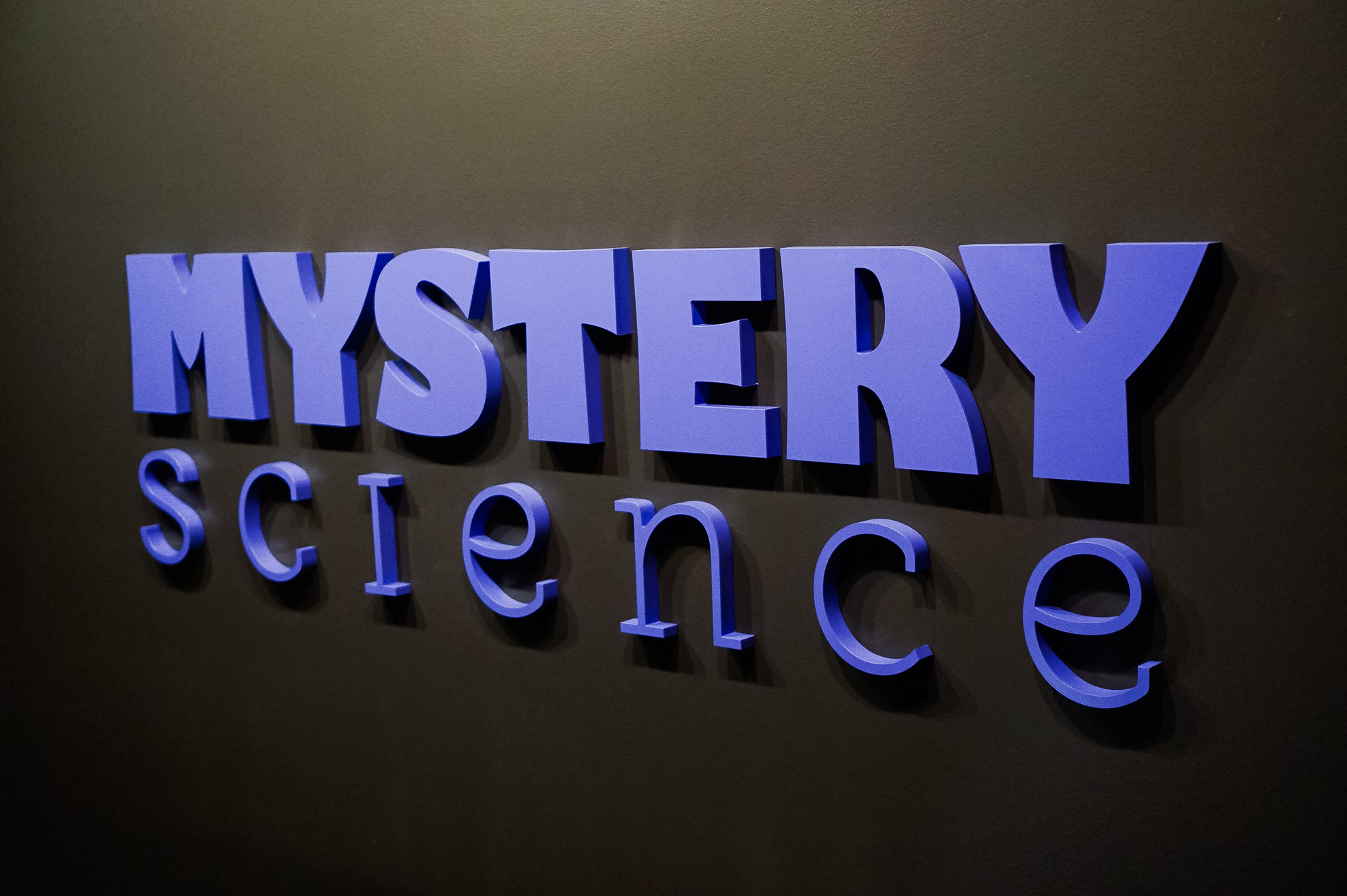Purple letters on dark grey wall for the Knotel designed Mystery Science lobby, a company that provides open-and-go lessons that inspire kids to love science.