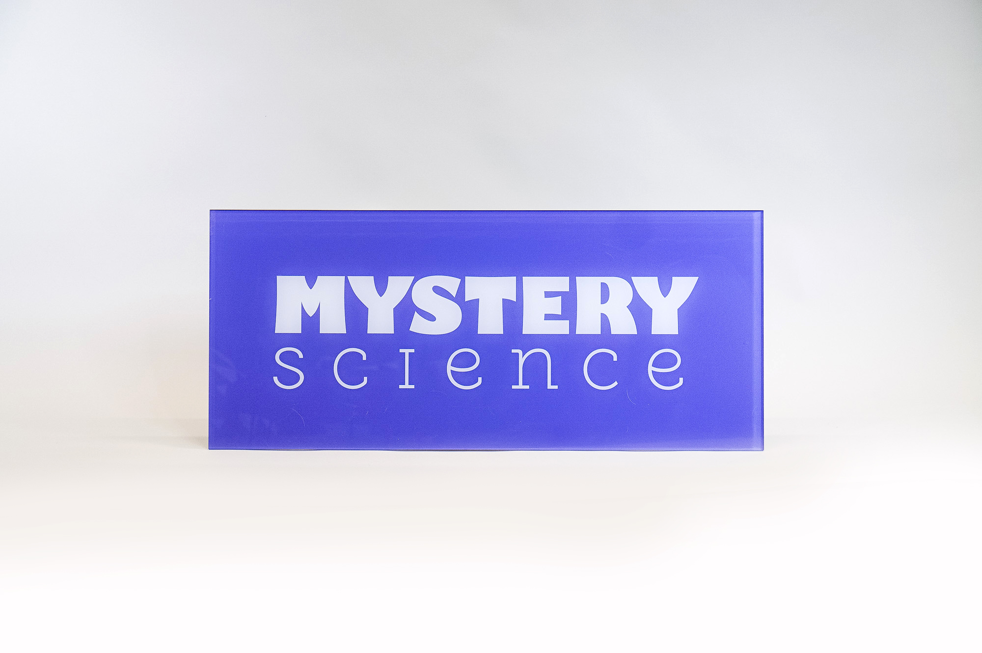 Glass-like colored panel sign for the Knotel designed Mystery Science lobby, a company that provides open-and-go lessons that inspire kids to love science.