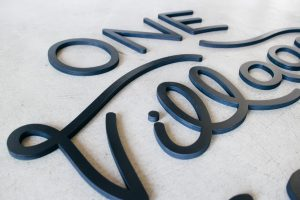 Black script sign for One Village Coffee, a specialty coffee roaster based in Souderton, PA.