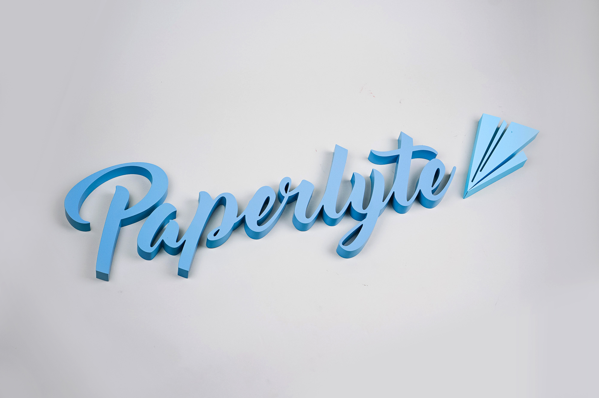 Blue dimensional script sign for Paperlyte, a media production company specializing in live streaming, video, documentary, and commercial content.