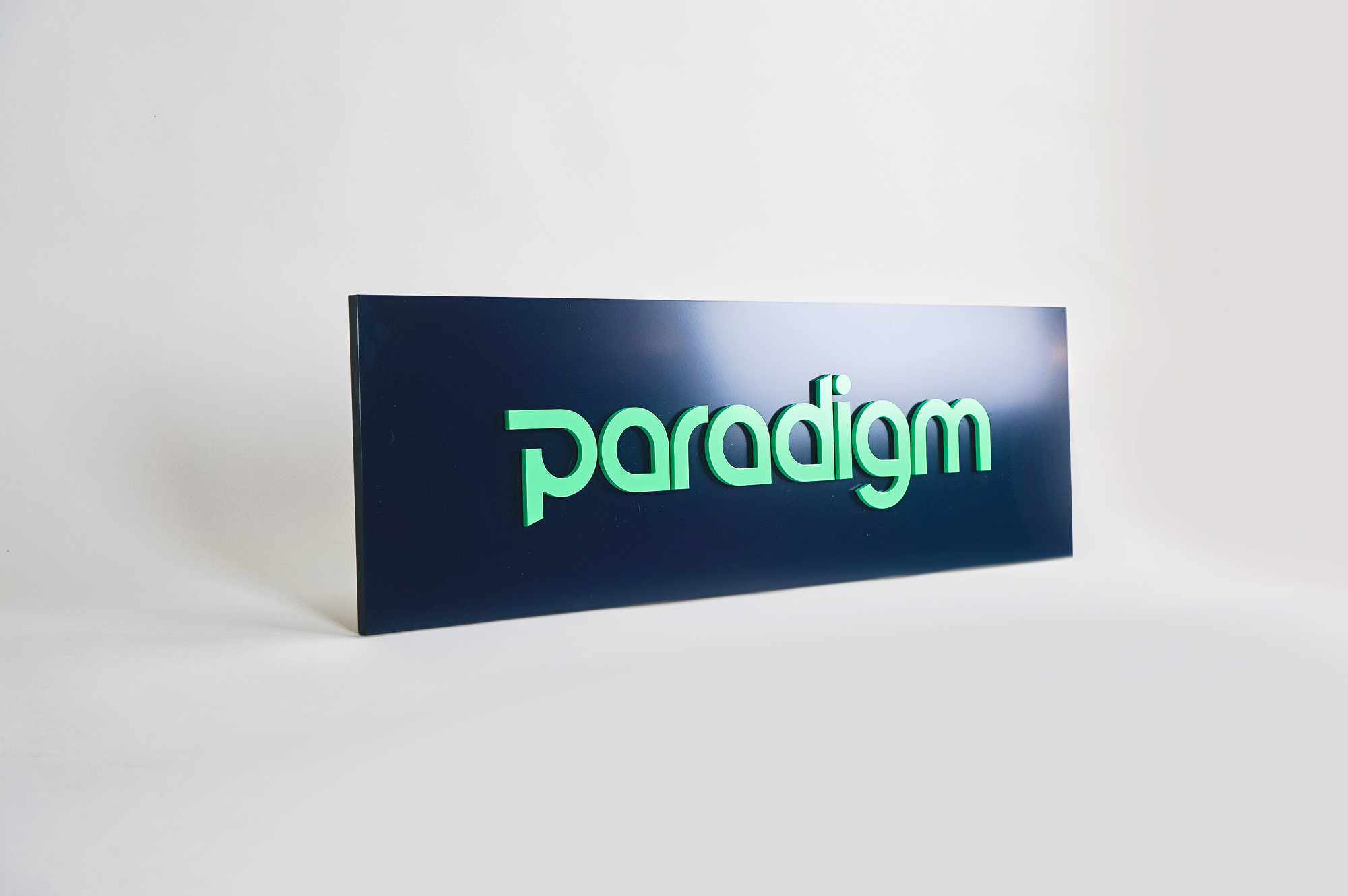 Green and navy, modern, raised text panel sign for Paradigm, a tech company currently located at WeWork in Oakland, CA.