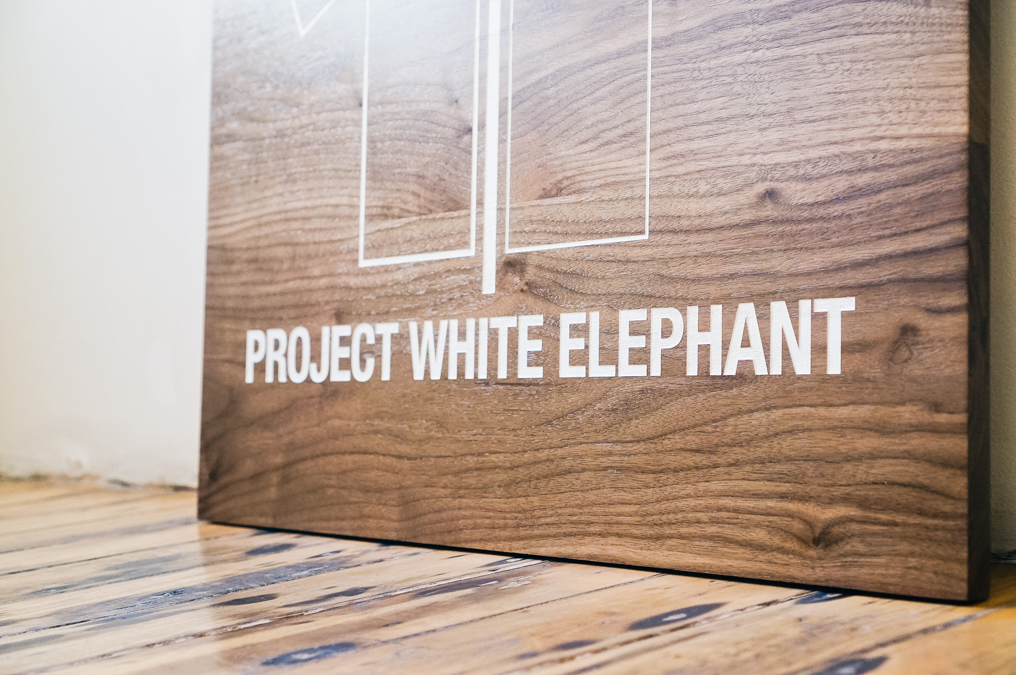 Solid walnut sign with white artwork for Project White Elephant, a womenswear brand based in San Francisco, California.