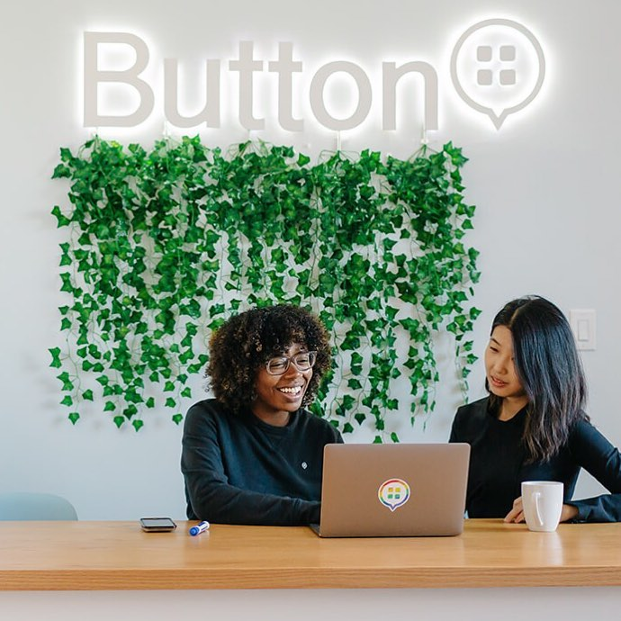 Illuminated, white halo-lit sign on white wall for Button
