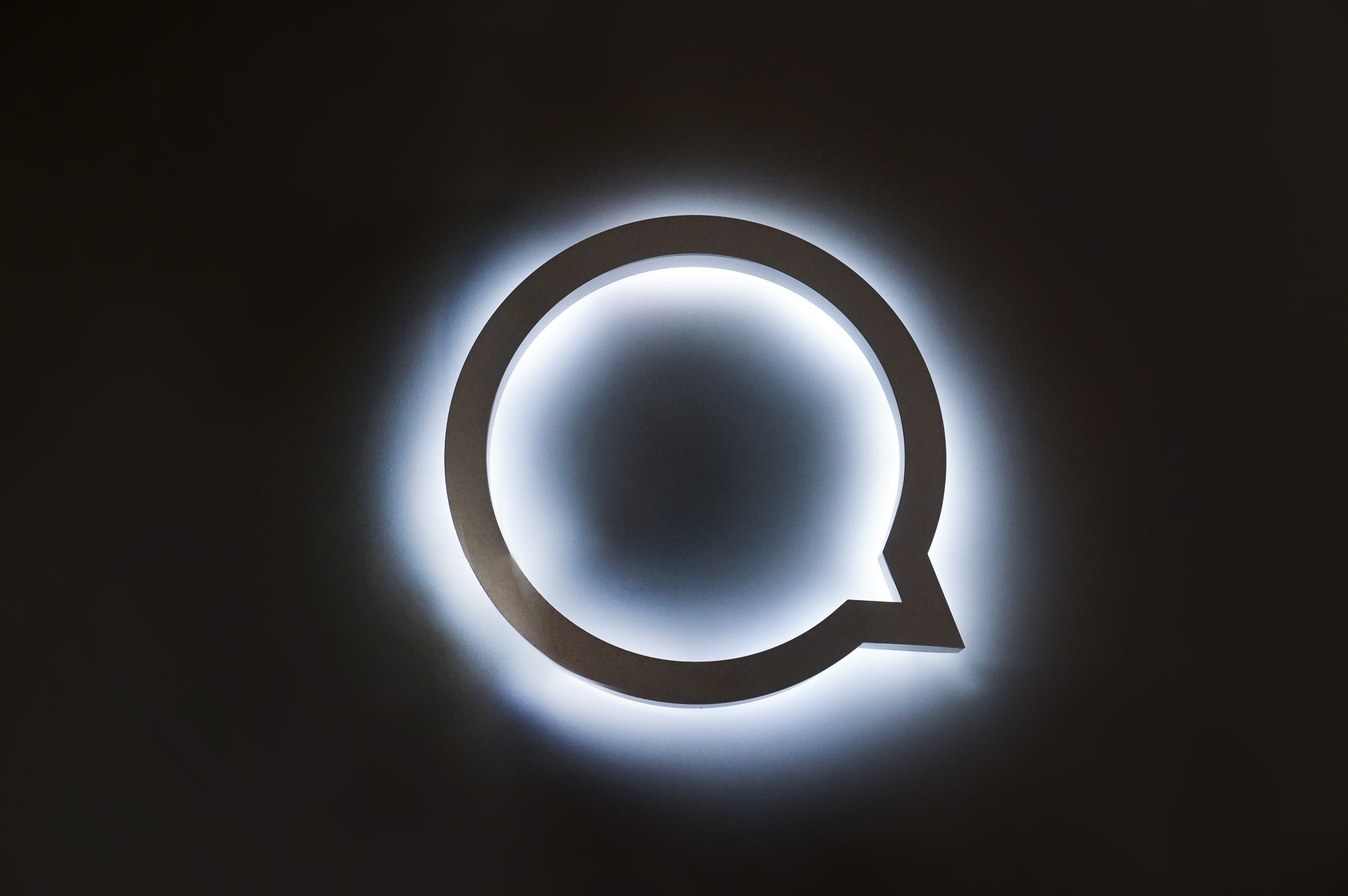 White halo lit illuminated sign for Button, a company that powers mobile partnerships.