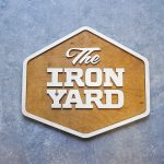Raised two-toned wood sign for The Iron Yard, a 12-week coding school offered in multiple cities across the US and in London.