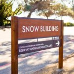 Wood national park style post sign for the snow building at the Oakland Zoo
