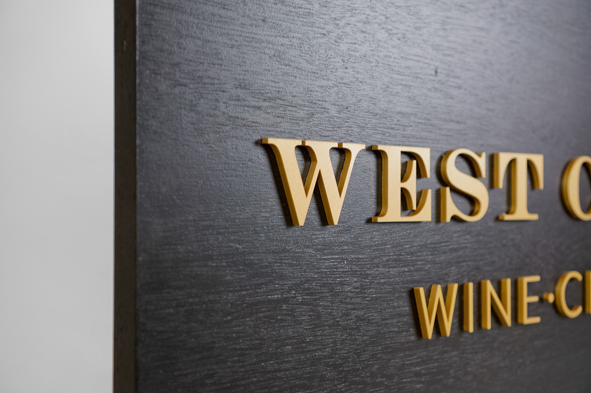Outdoor hanging sign for West Coast Wine and Cheese, a San Francisco based bar and gastropub.