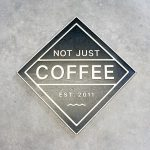 Black and light wood sign for Not Just Coffee