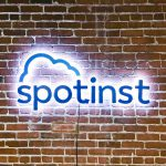 Illuminated, painted blue sign on brick conference room wall for Spotinst, a San Francisco company that creates intelligent workload software.