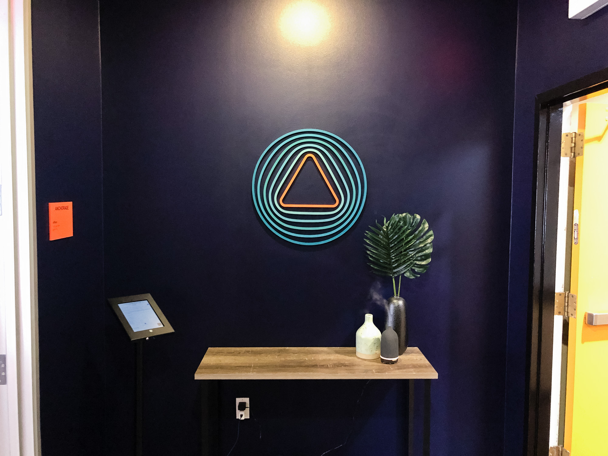 Painted, multi-color acrylic sign on a dark, navy blue wall for the entrance of Anchorage, a San Francisco-based company focused on creating custody solutions for the cryptocurrency ecosystem.