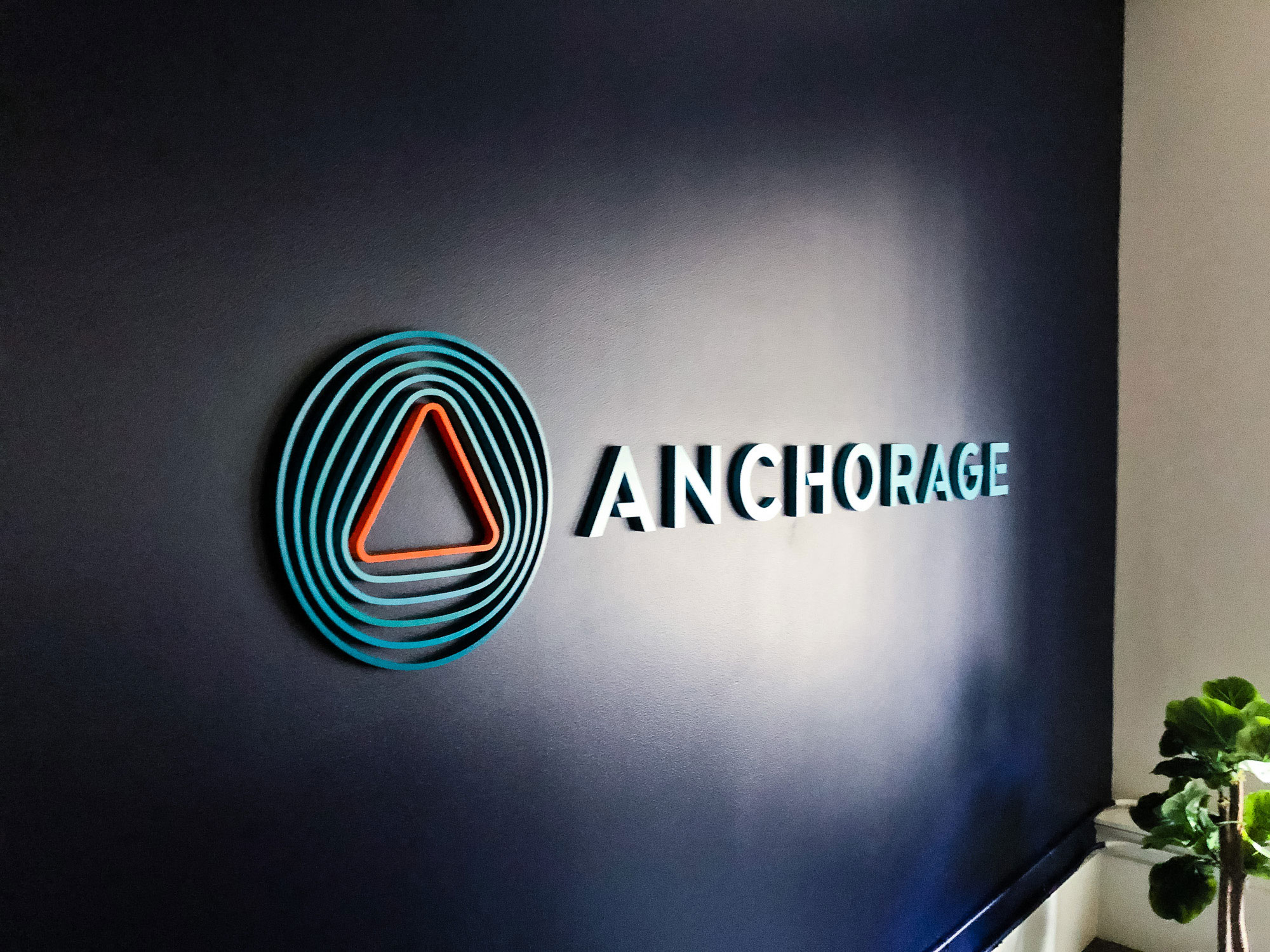 Painted, multi-color acrylic sign on a dark, navy blue wall for the lobby of Anchorage, a San Francisco-based company focused on creating custody solutions for the cryptocurrency ecosystem.