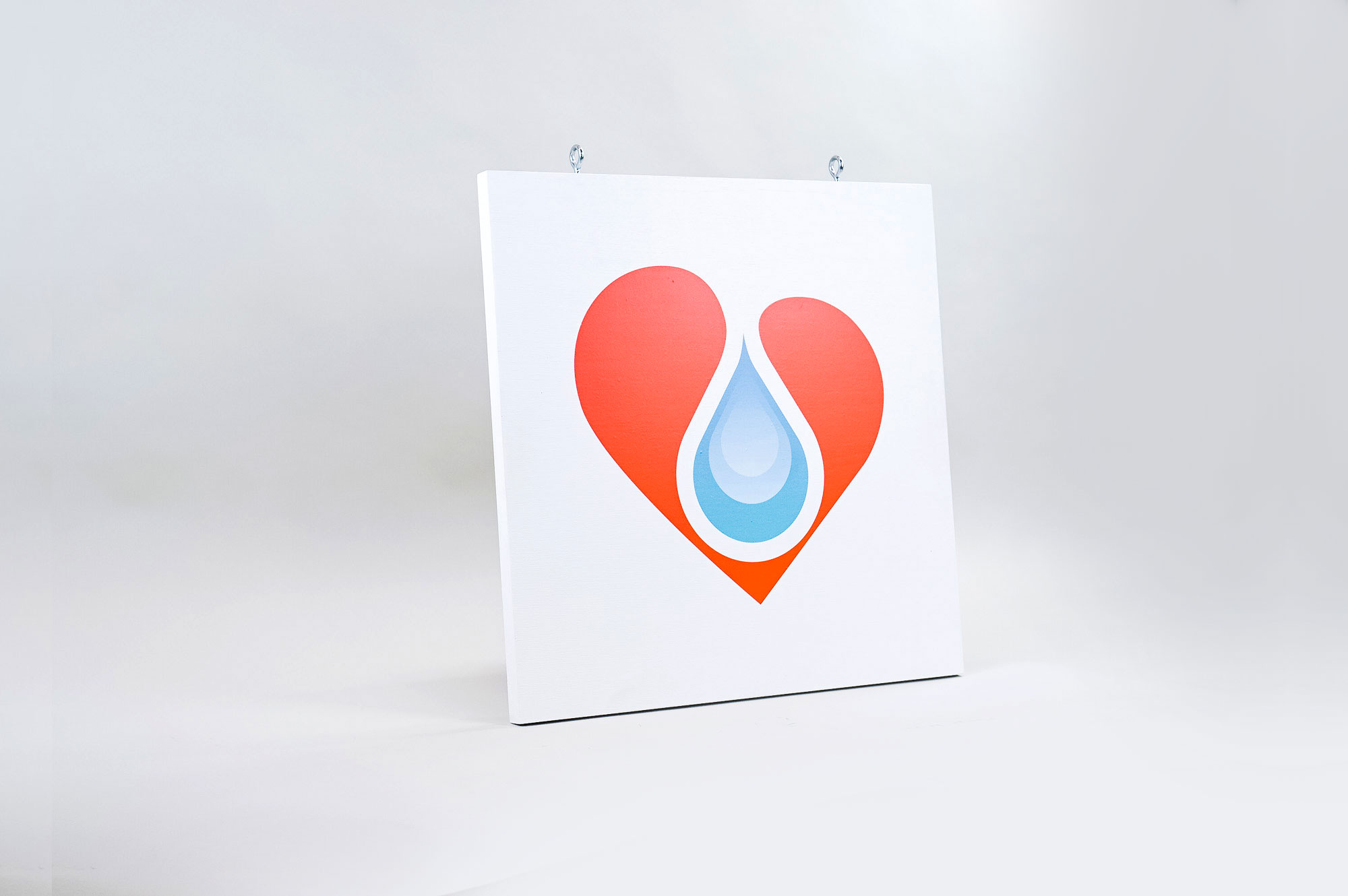 White hanging blade sign with colored logo for B12 LOVE, a San Francisco center offering nutrient therapies.