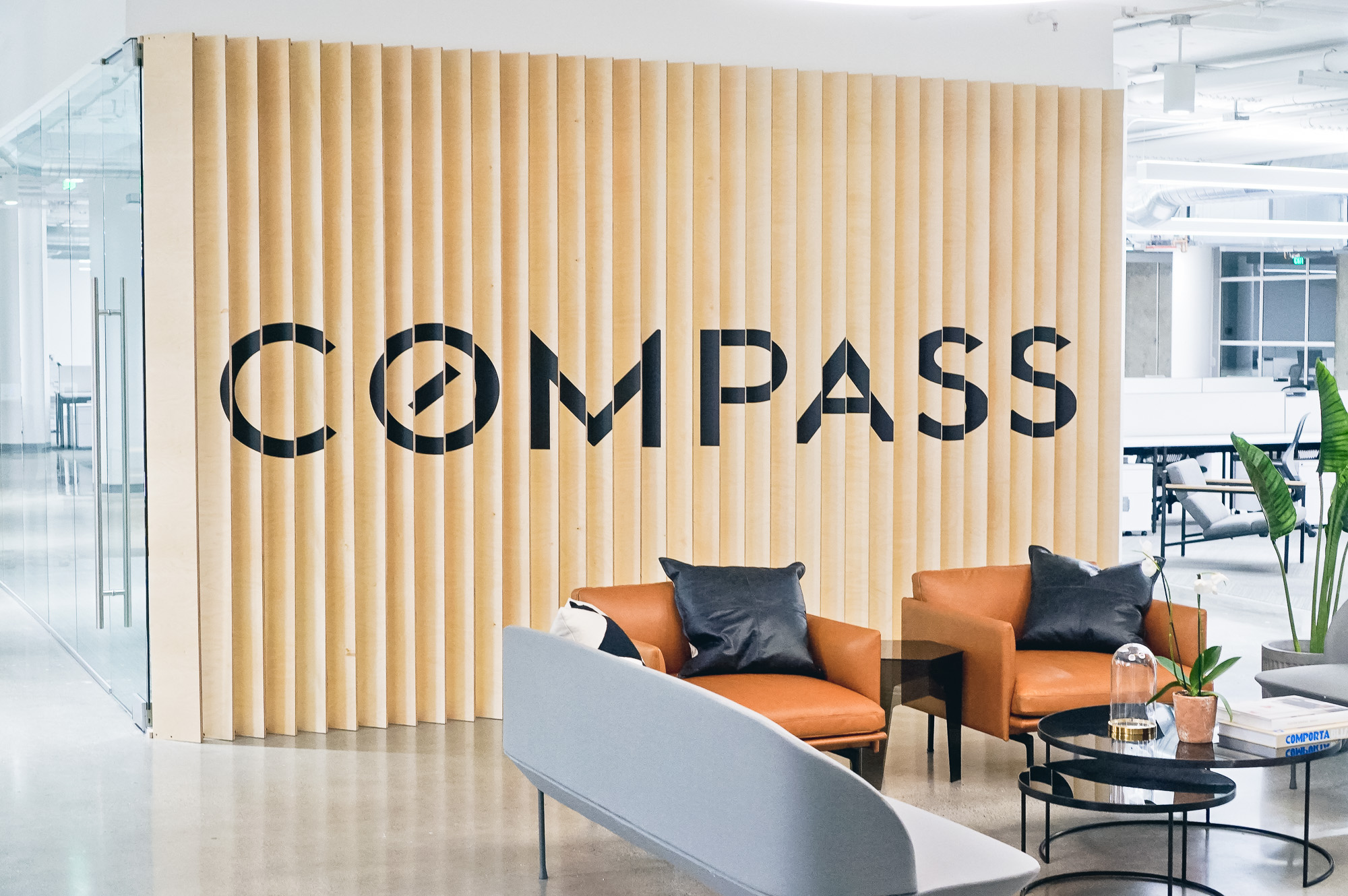 Optical-illusion, multi panel wood sign / privacy screen at the San Francisco office of Compass, a modern real estate platform.