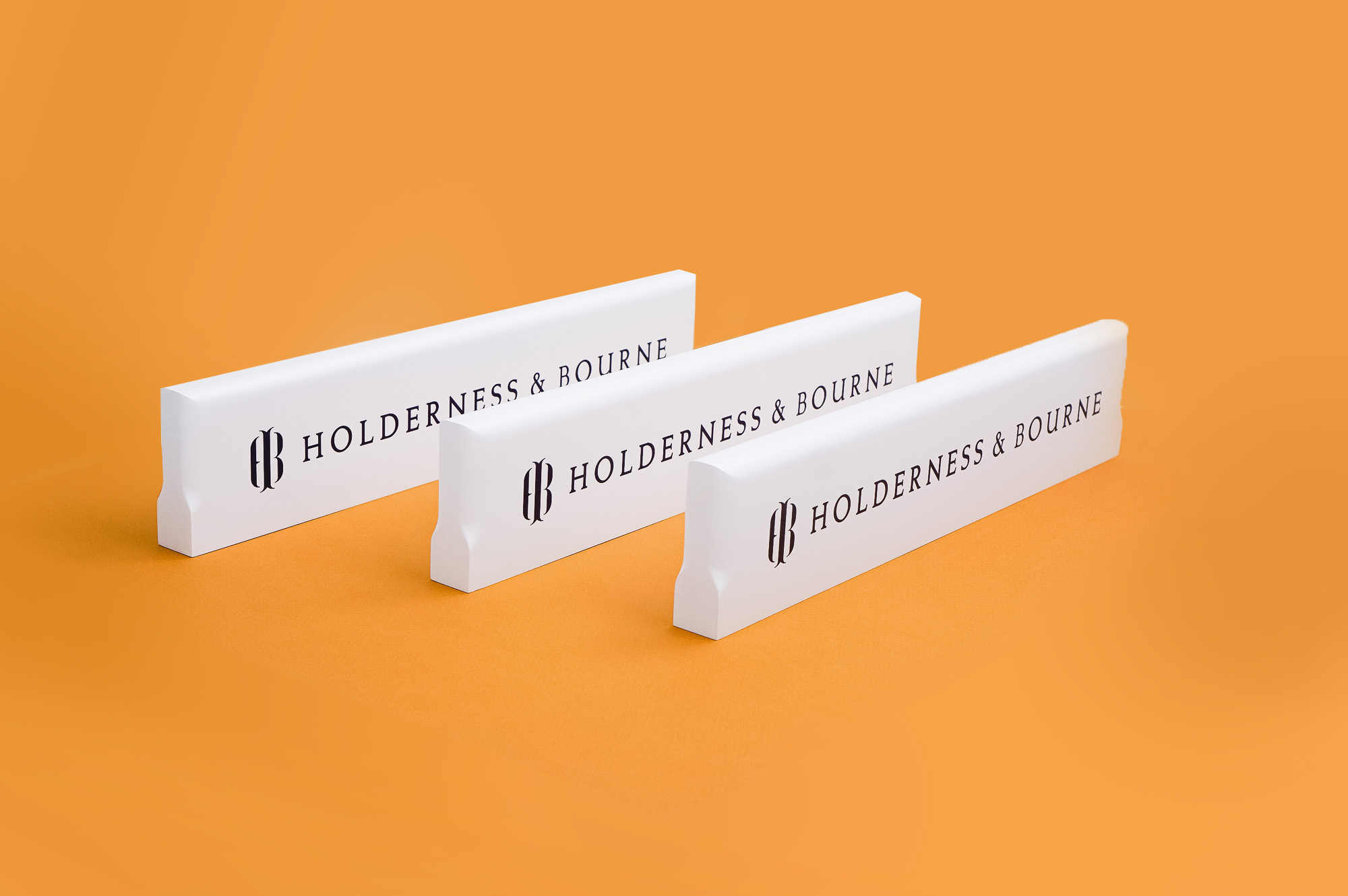 White and navy blue wood retail signs for Holderness & Bourne, a premium golf apparel and accessories company.