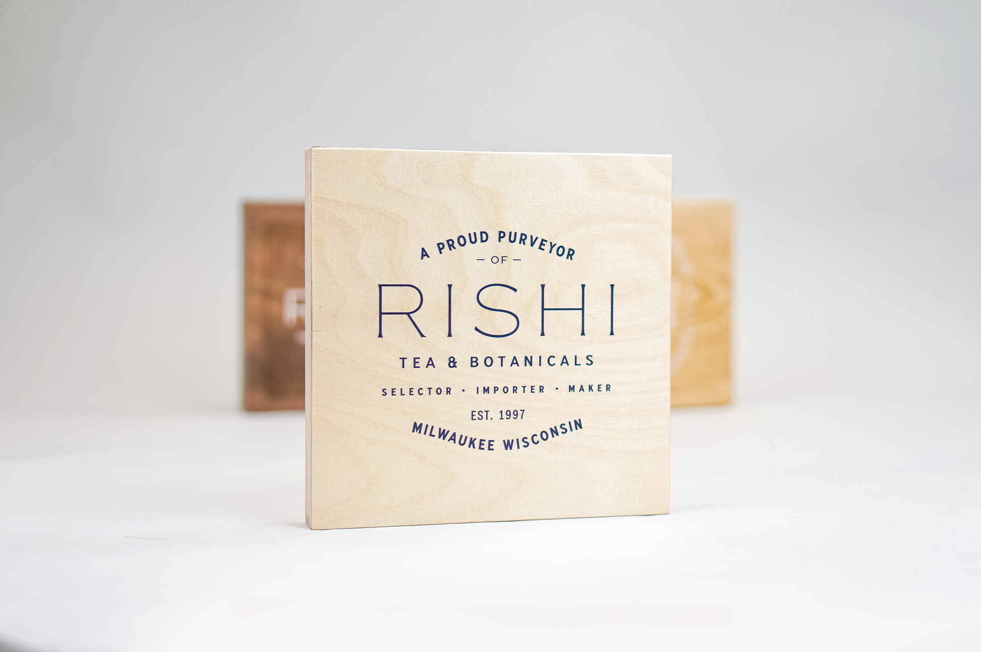 Plywood retail/cafe sign with white artwork for RIshi, a Direct Trade importer of organic teas and botanicals from the very best sources.