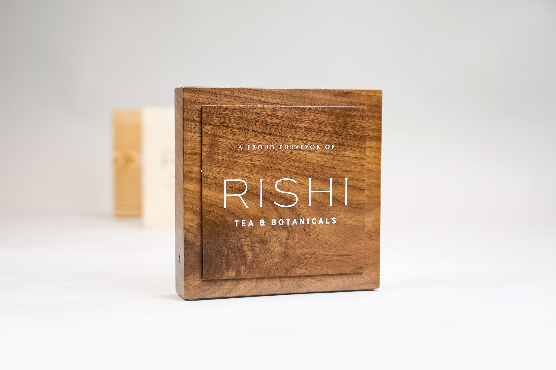 Solid walnut retail/cafe sign with white artwork for RIshi, a Direct Trade importer of organic teas and botanicals from the very best sources.