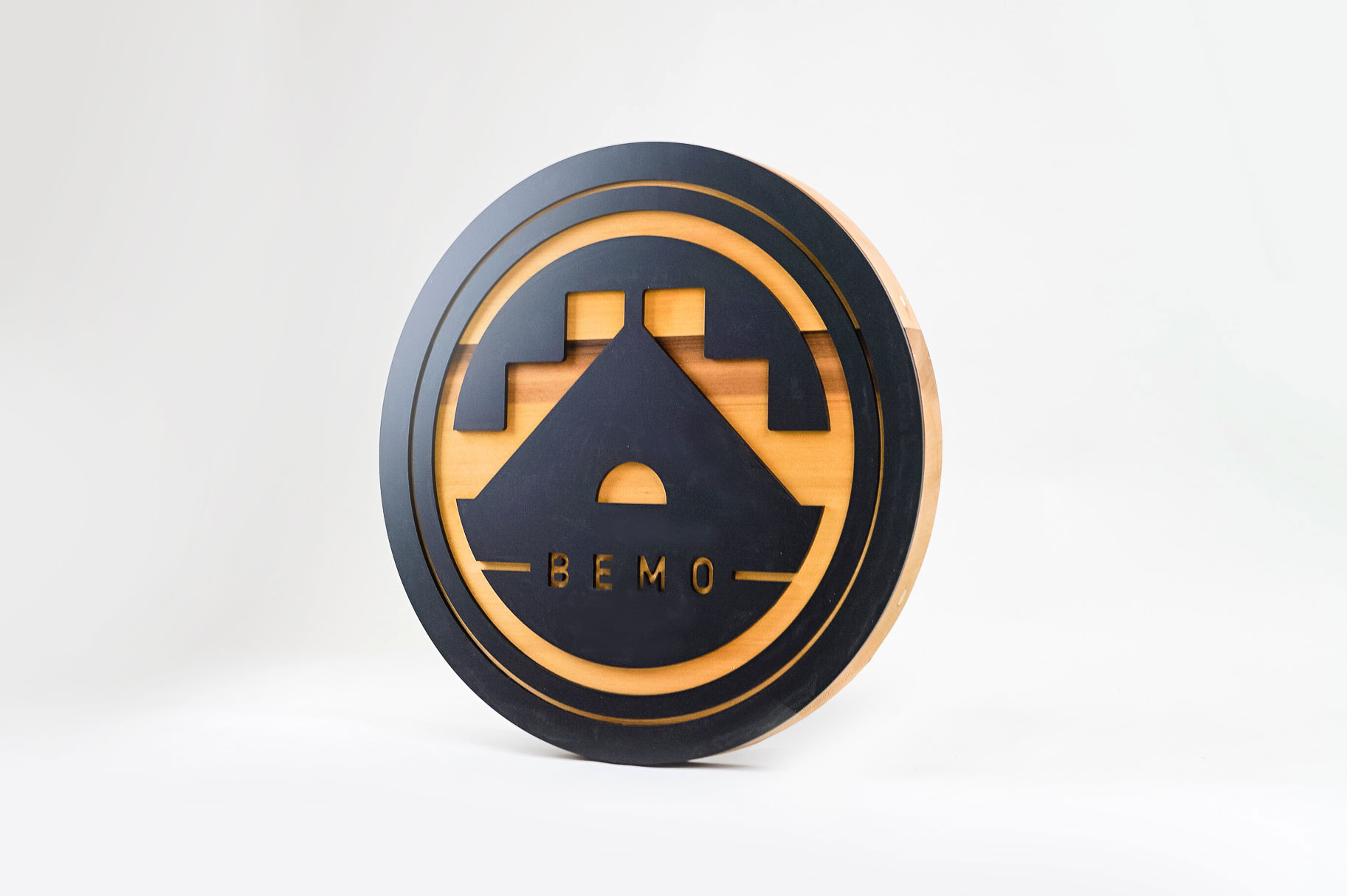Raised matte black and cedar round exterior sign for BEMO, a Los Angeles based creative studio specializing in VFX, Animation and Immersive Content.