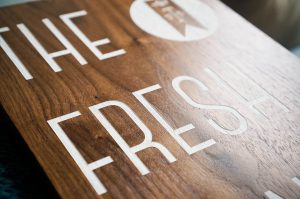walnut sign with white text for the fresh prints