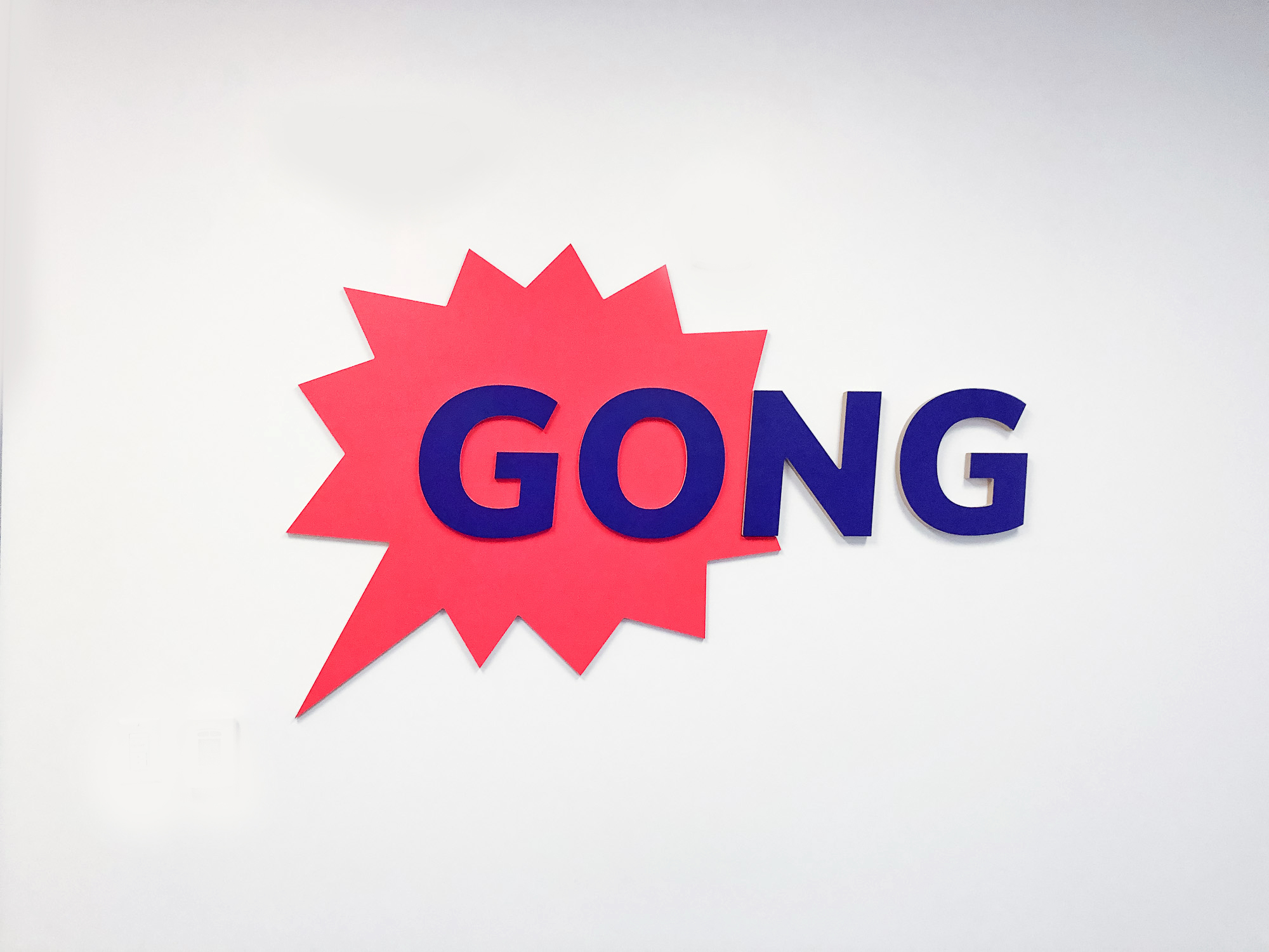 Red and purple painted sign for the San Francisco office of Gong, makers of a conversation intelligence platform for sales.