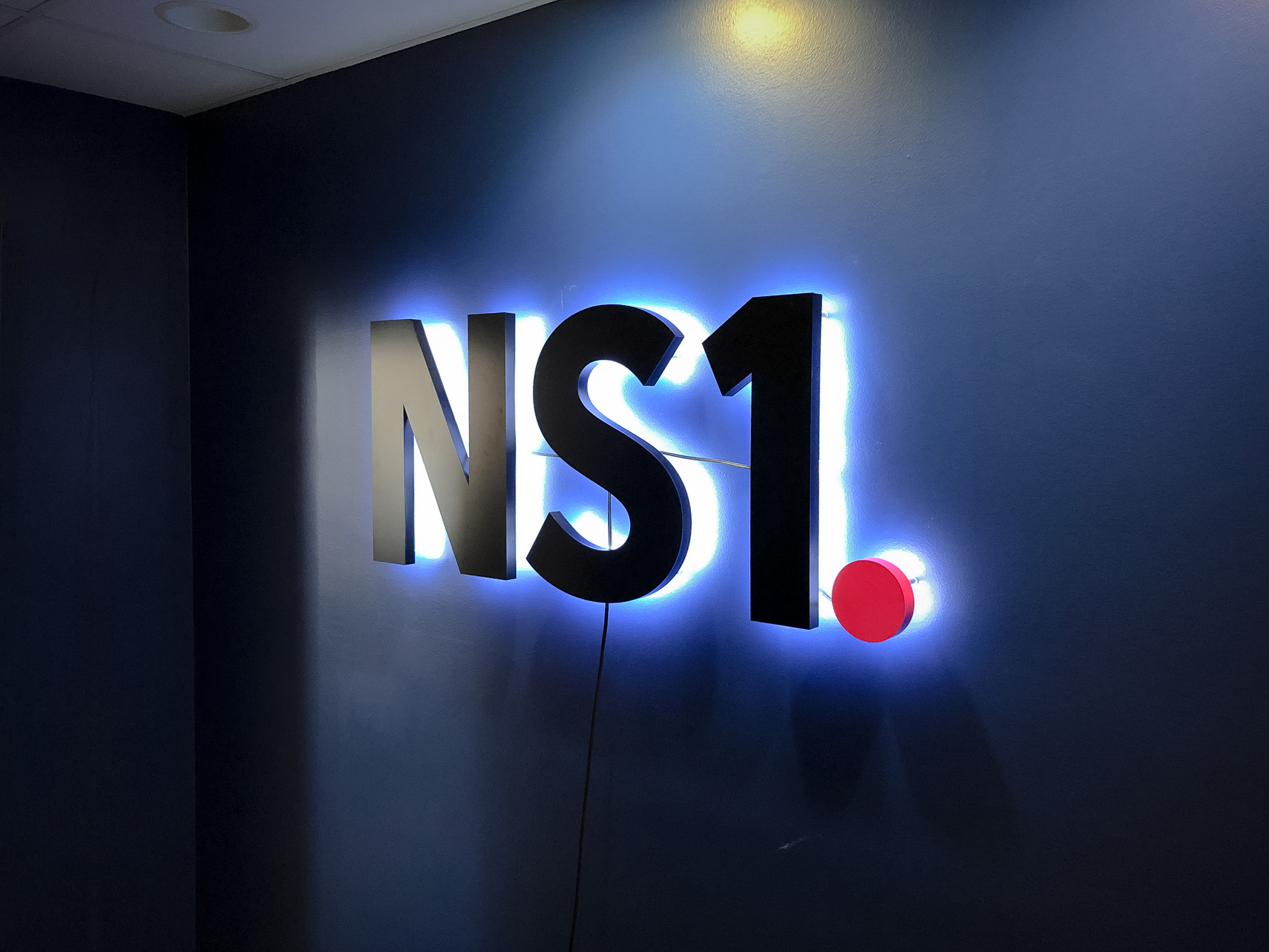 NS1 halo lit sign on dark blue wall