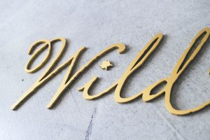 brushed gold sign for wild ink press