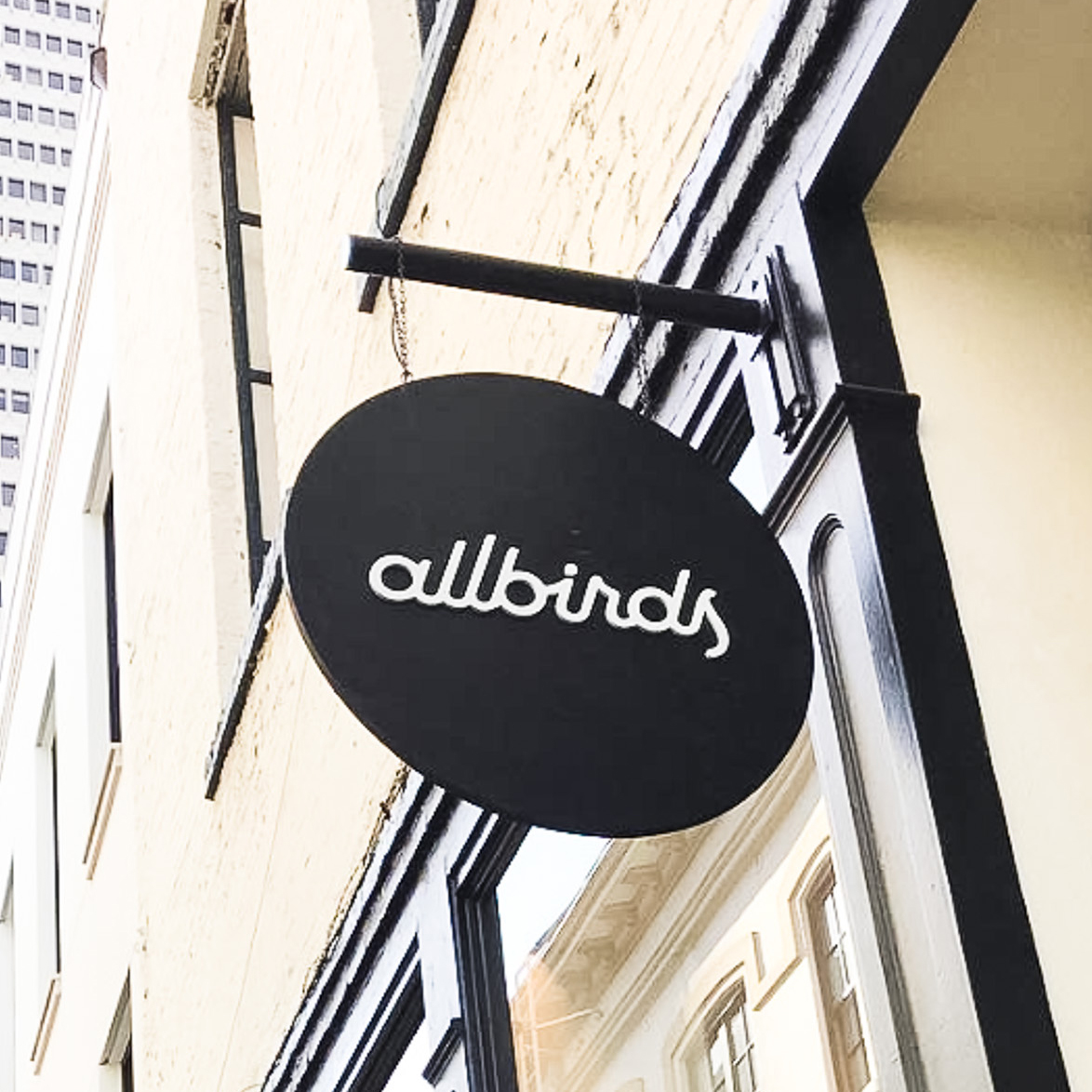Black round blade sign with white script text for Allbirds, a San Francisco-based direct-to-consumer startup aimed at designing environmentally friendly footwear.