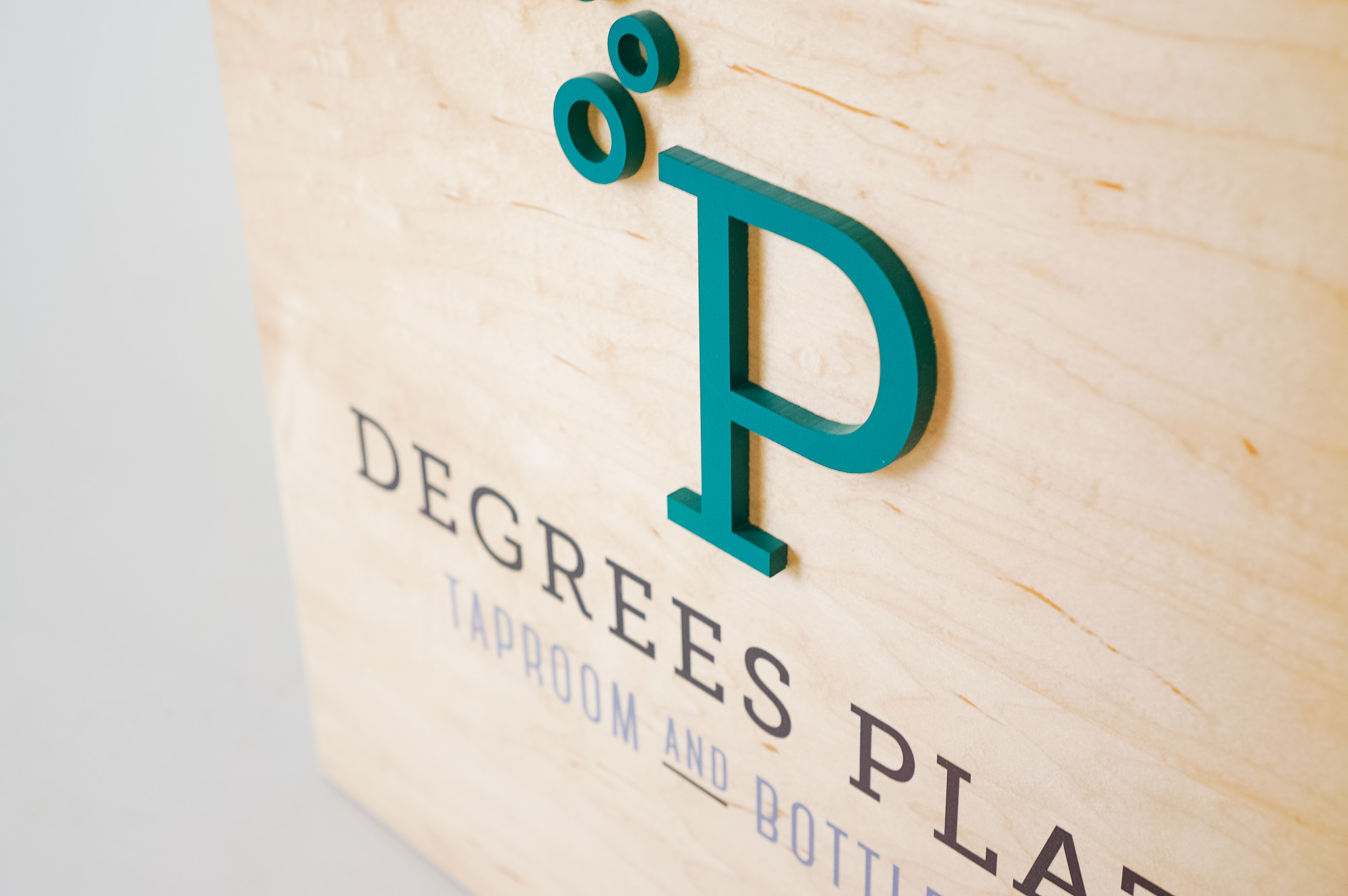 Light wood menu sign for Degrees Plato, a family-friendly Latin kitchen & locally focused craft beer bar in Oakland, CA.