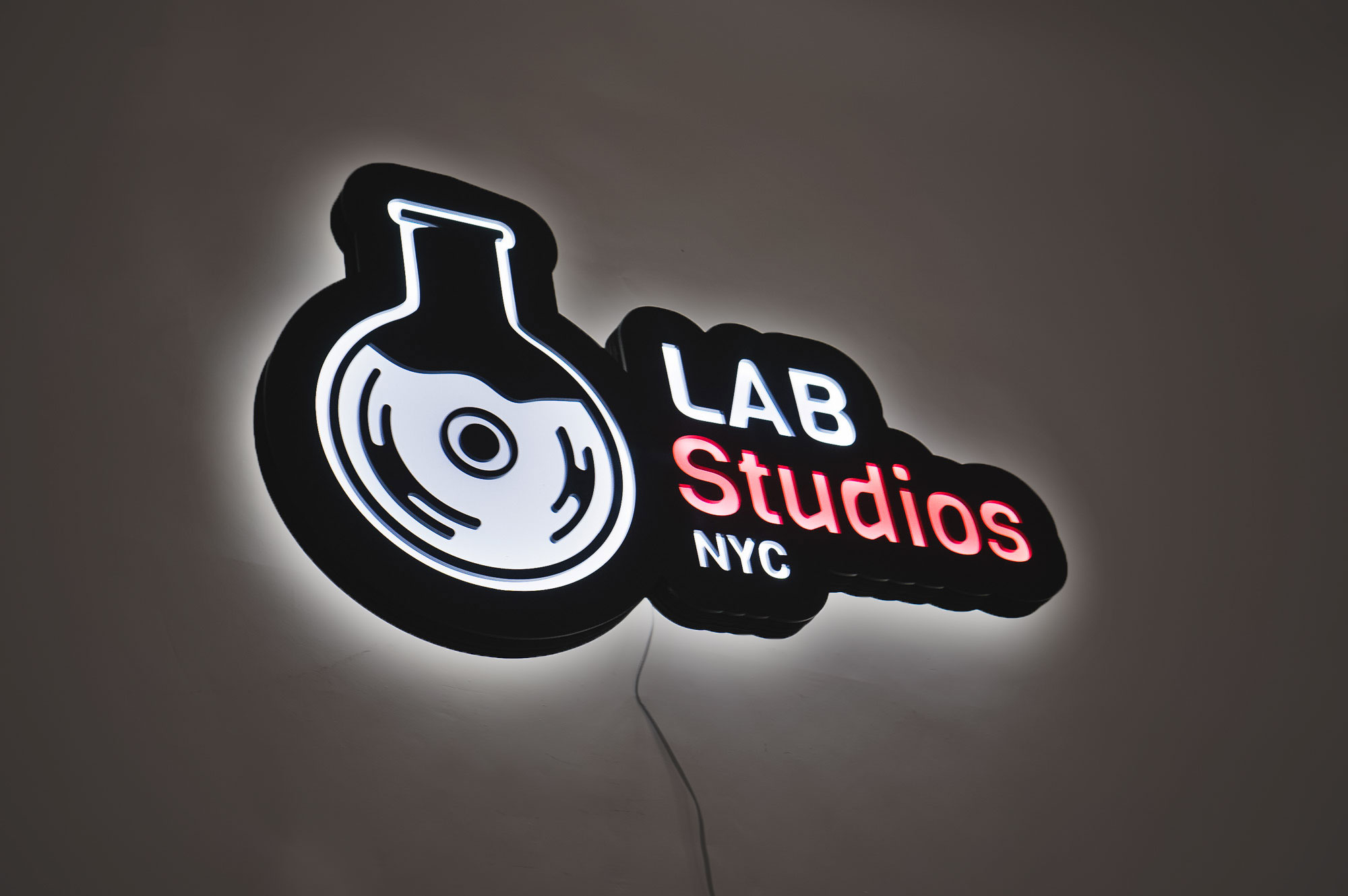 Illuminated pink, white, and black lightbox sign for Lab Studios, a recording studio in New York City.