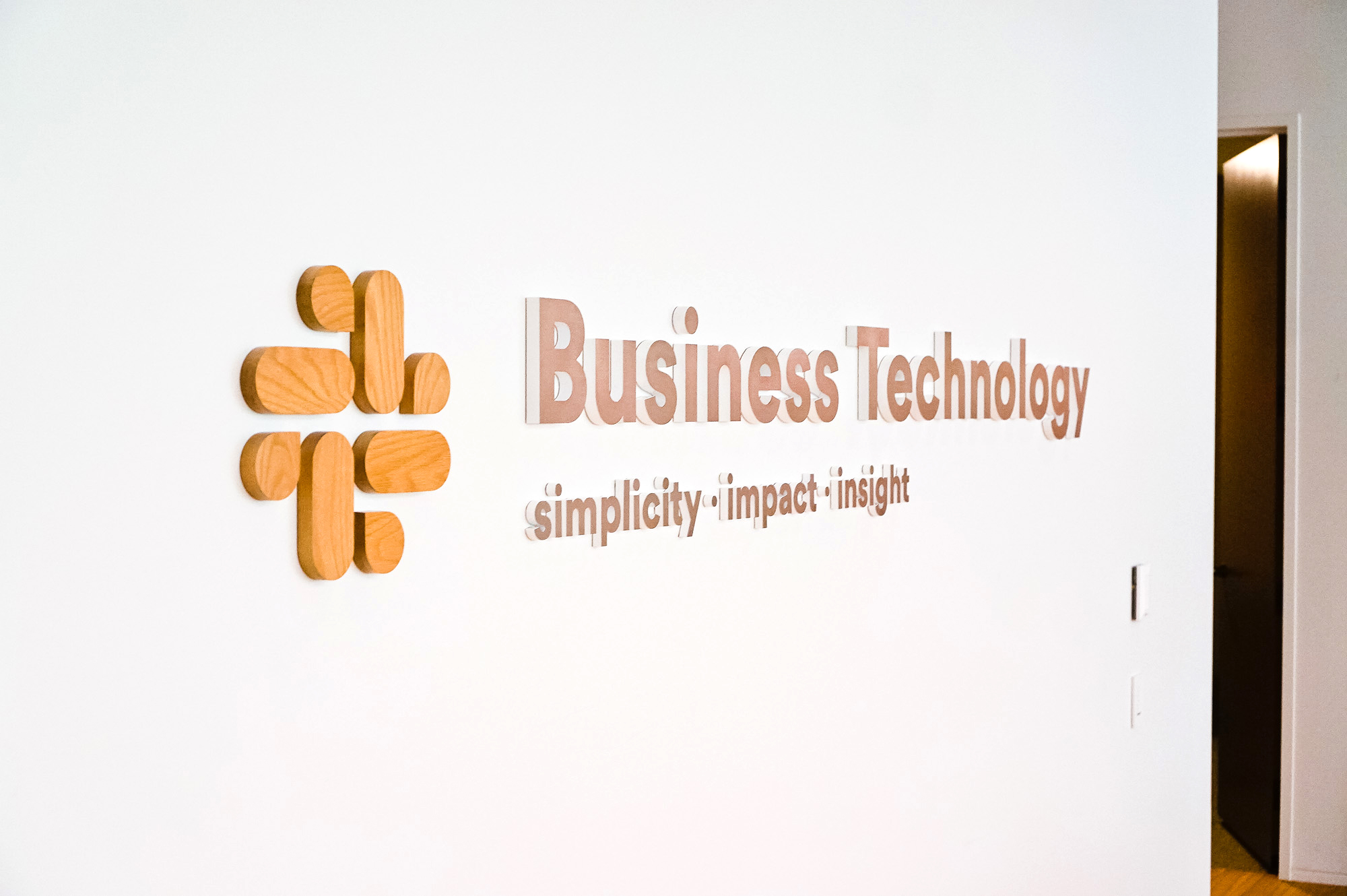Wood and metal sign for the Business Technology department at Slack, an American cloud-based set of team collaboration tools and services.