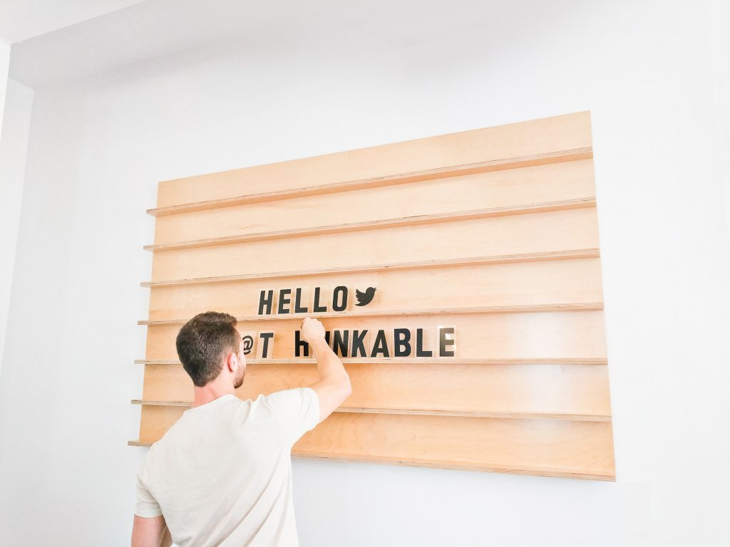 Wood message board with rails and clear letters for the office of Thunkable, a cross-platform app builder that enables anyone to build their own native mobile apps.