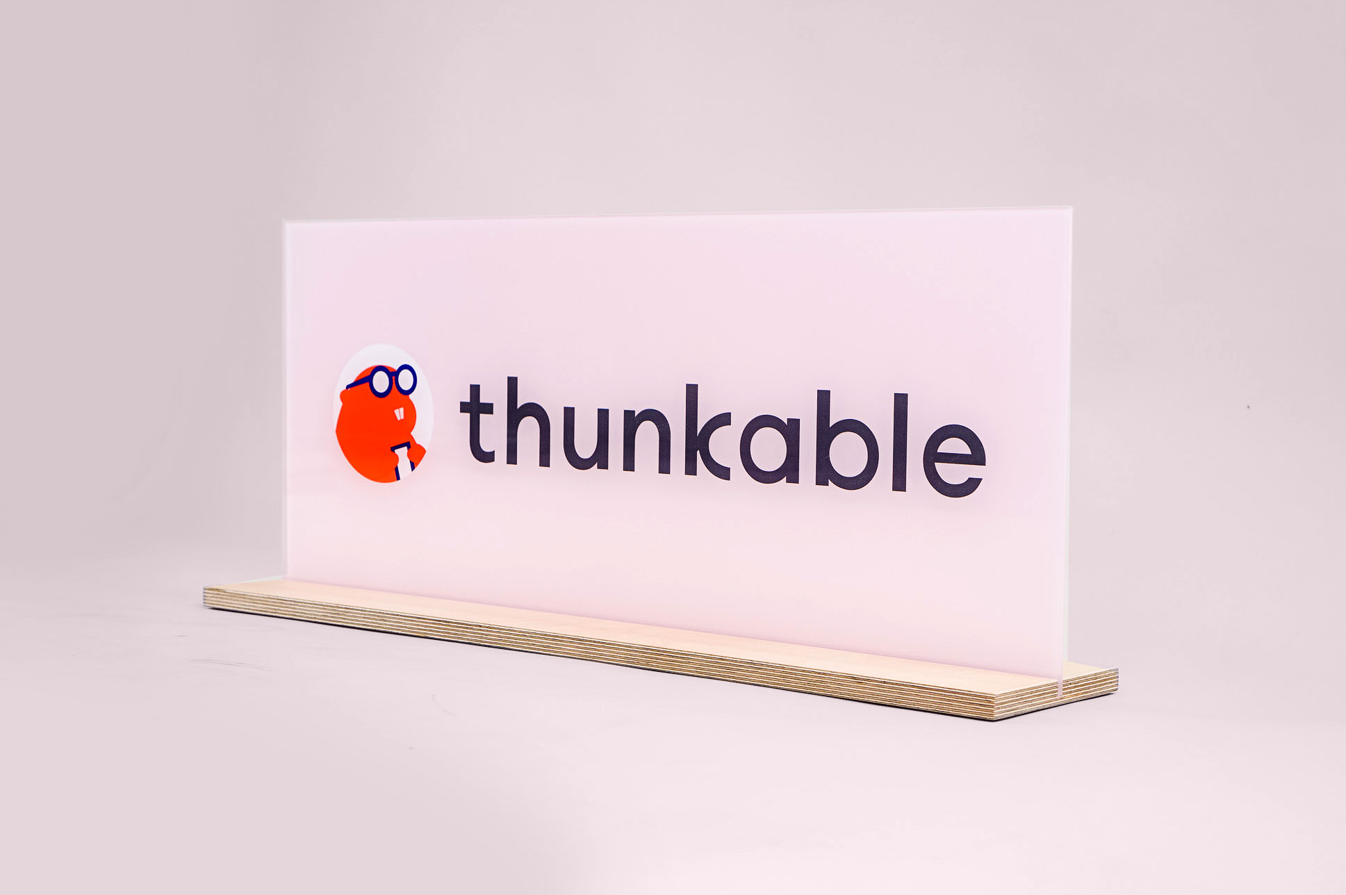 Glass-like, pink freestanding back printed sign for Thunkable, a cross-platform app builder that enables anyone to build their own native mobile apps.