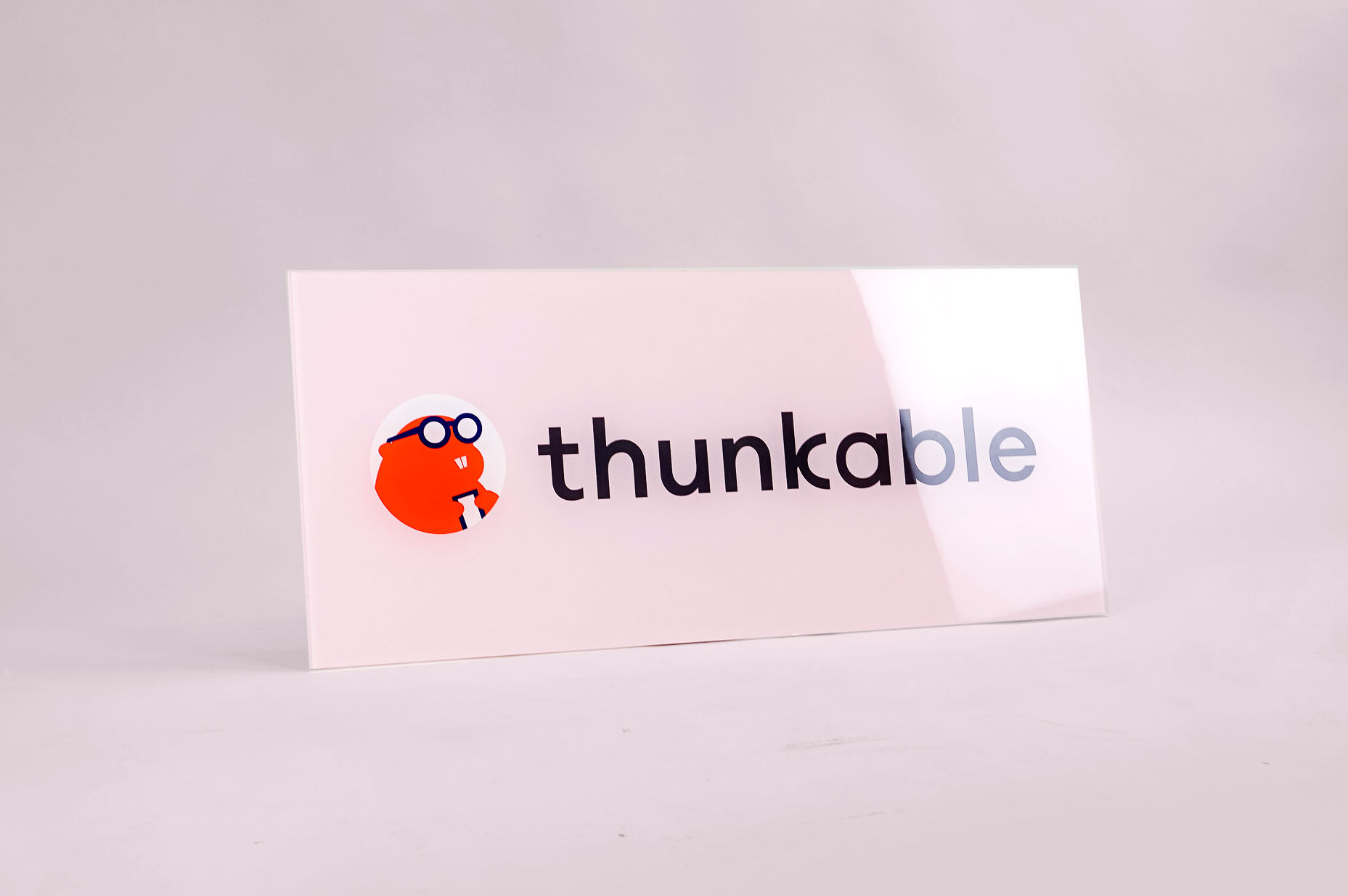 Glass-like, pink back printed sign for Thunkable, a cross-platform app builder that enables anyone to build their own native mobile apps.