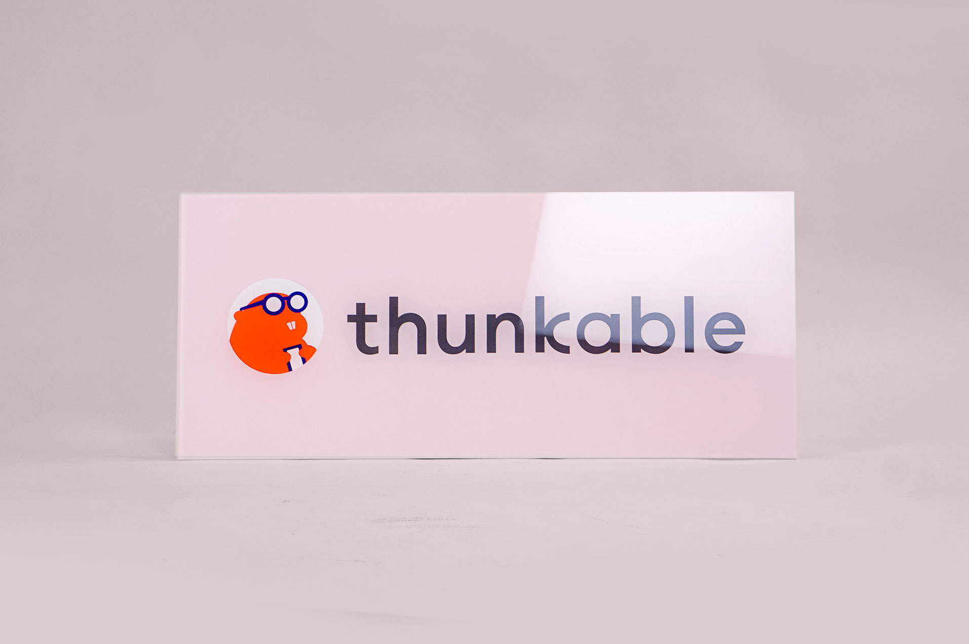 Glass-like, pale pink back printed sign for Thunkable, a cross-platform app builder that enables anyone to build their own native mobile apps.